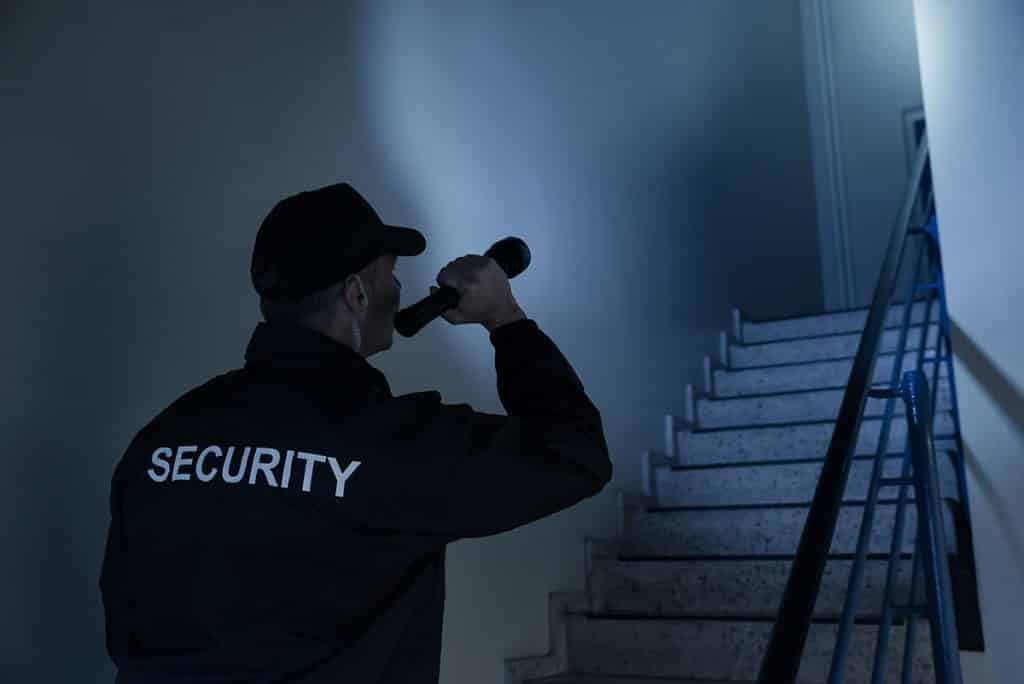Business security guard inspecting alarm response in dark hallway